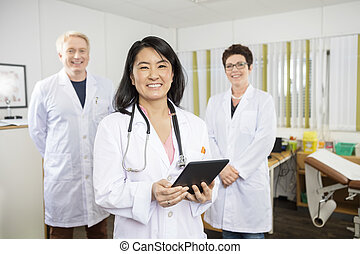 Happy Doctor Holding Tablet Computer While Standing With Colleag