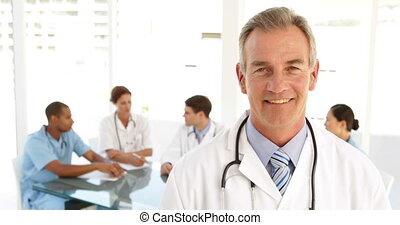 Happy doctor looking at camera and his staff behind him at...