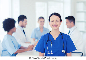 clinic, profession, people and medicine concept - happy female doctor over group of medics meeting at hospital