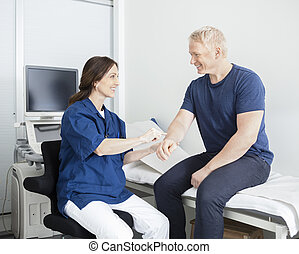Happy Doctor Touching Male Patient's Hand In Clinic
