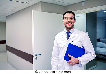 happy doctor with clipboard at hospital corridor