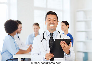 happy doctor with clipboard over medical team - clinic,...