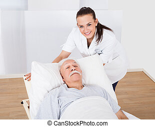 Happy Doctor With Senior Man Lying In Bed