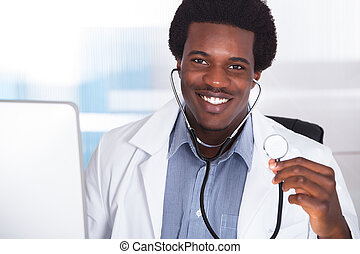 Happy Doctor With Stethoscope Sitting At A Desk
