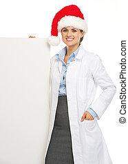 Happy doctor woman in santa hat showing blank billboard