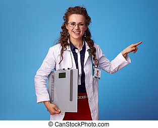 happy doctor woman with scales pointing at something on blue