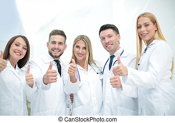 Happy doctors smiling and showing thumbs up.