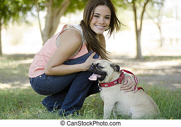 Cute young woman and her pug dog spending some time together at a park