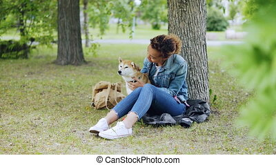 Happy dog owner attractive African American girl is stroking...