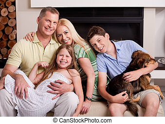 Happy domestic family sitting in living room with dog