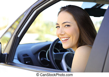 Happy driver looking at you inside a car
