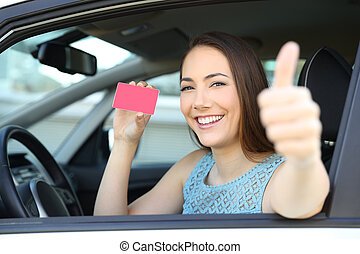 Happy driver showing card or license with thumbs up