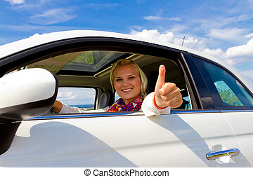 Happy driver - Young woman in her new car, with thumb up