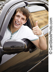 happy driving - teen driver in good mood with black car,...