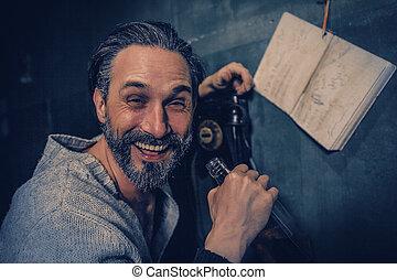 Happy drunk man talks on a vintage rotary telephone