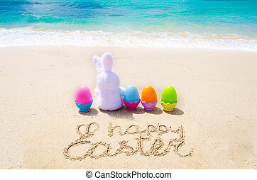 Happy easter background with color eggs on the beach