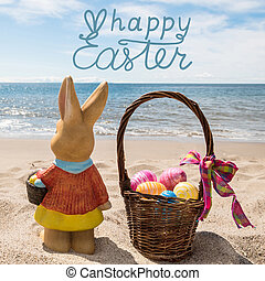 Happy Easter bunny with basket and color eggs on the ocean beach