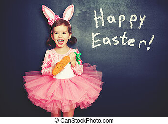 Happy Easter! child girl in  costume bunny with carrot about blackboard