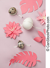 Happy Easter concept. Flat lay. Minimal concept. Top view. Set of eggs with scotch tape and coral origami papercraft flowers on pink background