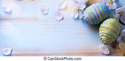 Happy Easter; Easter eggs and sprig flowers on blue table ...