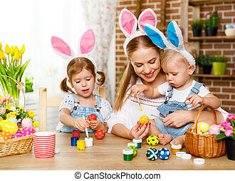 Happy easter! family mother and children paint eggs for holiday Easte
