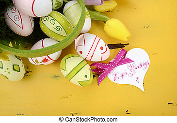 Happy Easter green and yellow felt basket of of pink, white and green easter eggs on rustic vintage yellow wood table, with heart shape greeting card.