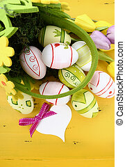 Happy Easter green and yellow felt basket of of pink, white and green easter eggs on rustic vintage yellow wood table, with heart shape greeting card, vertical.