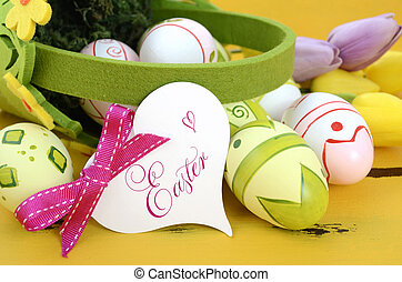 Happy Easter green and yellow felt basket of of pink, white and green easter eggs on rustic vintage yellow wood table, with heart shape greeting card, closeup.