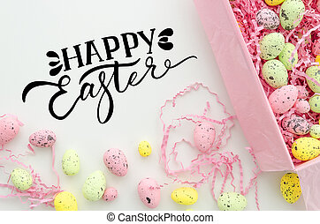 Happy easter hand lettering greeting card design. Colorful Easter eggs in a box on white table, top view. Easter flat lay.