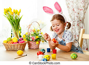 Happy easter! happy baby girl paints eggs for holiday