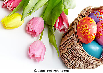 Image of colored Easter eggs in basket and bunch of tulips near by