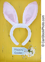 Happy Easter pink and white bunny ears on yellow wood background.