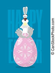 Happy Easter. Rabbit and Easter egg. Traditional treats for Easter. Colored eggs. Funny Bunny sitting on egg. Symbol of Easter holiday