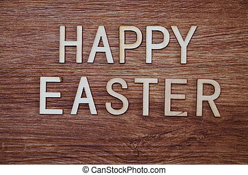 Happy Easter text message on wooden background