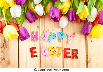 Happy Easter written in multicolored letters and fresh...