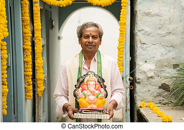 happy Elder man with Ganesha Idol coming home during ganesha or vinayaka Chaturthi festival - Concept of indian religious festival celebration