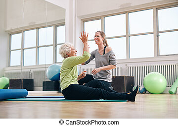 Happy elder woman rejoicing health success with her trainer