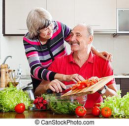 happy  elderly couple cooking  in kitchen