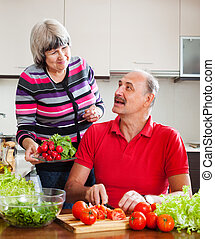 happy elderly couple cooking  lunch in  kitchen