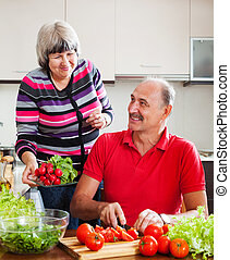happy elderly couple cooking vegetables