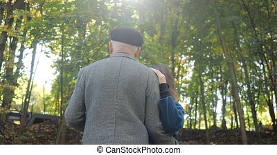 Happy elderly couple dancing on the alley of a beautiful park in the autumn - slow motion.