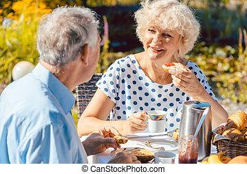 Happy elderly couple eating breakfast in their garden...