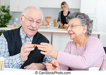 happy elderly couple eating dinner
