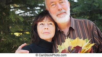 Happy elderly couple enjoy hugging in autumn under a pine tree - slow motion.