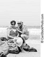 Happy elderly couple enjoying their retirement vacation near the sea