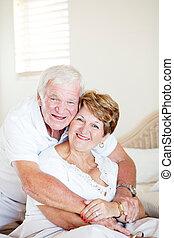 happy elderly couple hugging in bedroom