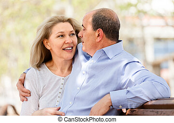 happy elderly couple hugging on a bench