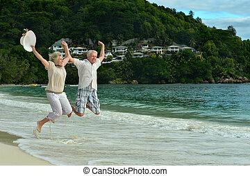 elderly couple jumping on the beach