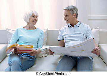 Happy elderly couple reading while sitting together