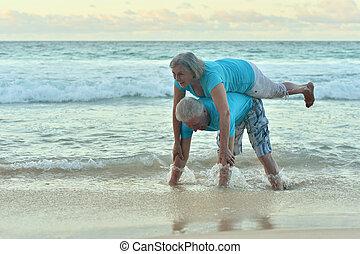 Happy elderly couple resting on  beach